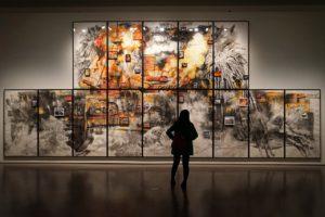 человек смотрит на картину на художественной выставке